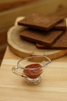 Molheira de vidro com ketchup na mesa de madeira