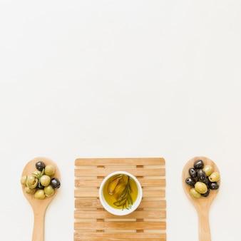 Molheira na almofada quente com azeitonas em colheres