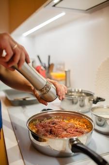 Molho à bolonhesa, cozinhe adiciona pimenta. ficamos em casa e cozinhamos lasanha na cozinha.
