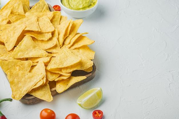 Molho caseiro de guacamole e queijo com nachos, em mesa branca