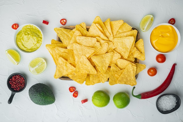 Molho caseiro de guacamole e queijo com nachos, na mesa branca, vista de cima ou plano