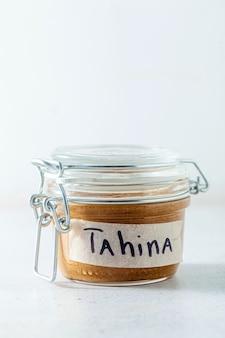 Molho caseiro de tahine com gergelim em uma jarra lacrada sobre a mesa