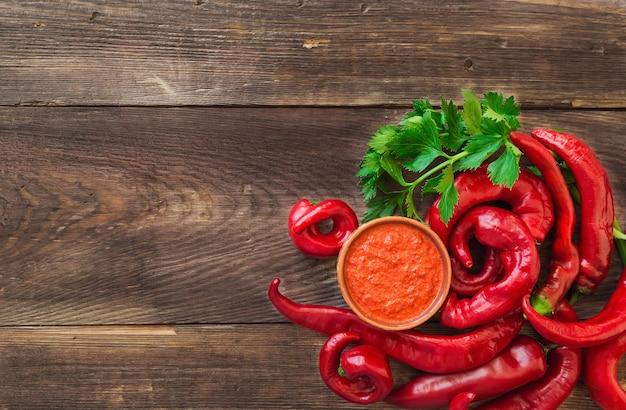 Molho caseiro e red hot chili peppers e aipo na superfície de madeira rústica. vista do topo.