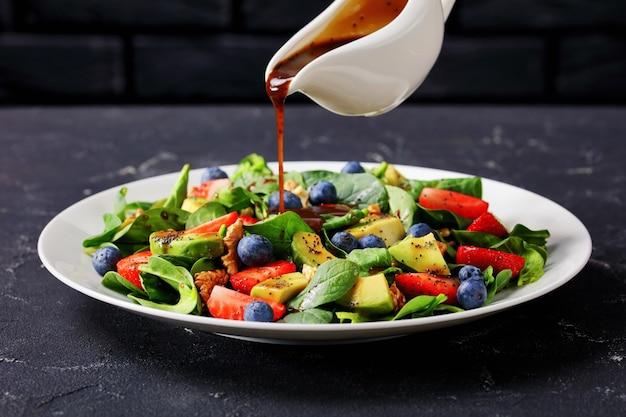 Molho caseiro servido sobre espinafre fresco, nozes, abacate, morango e salada de mirtilo em um prato branco