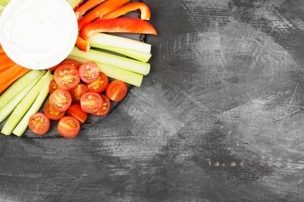 Molho cremoso em uma tigela branca e vários legumes
