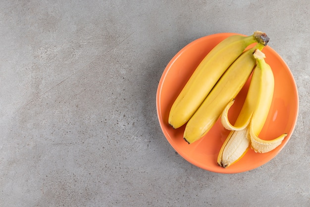 Molho de banana amarela suculenta colocada em uma superfície de pedra