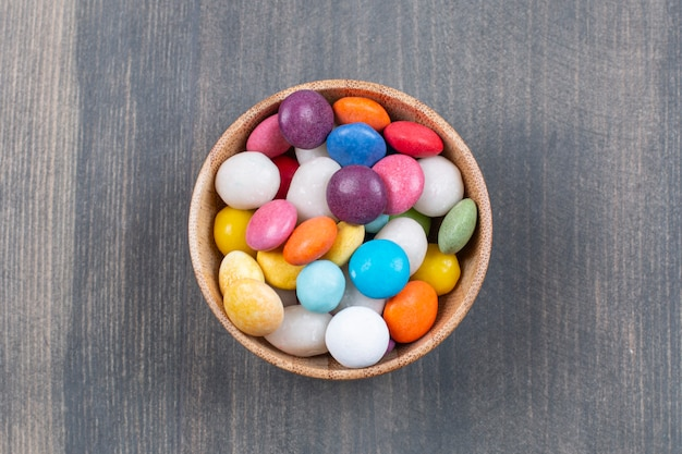 Molho de bombons coloridos em tigela de madeira