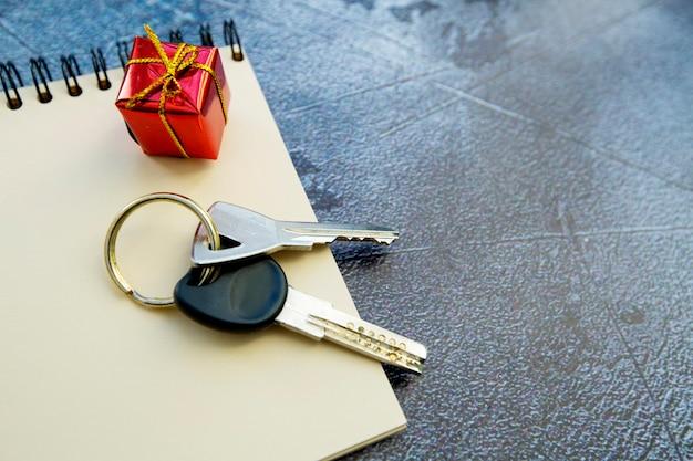 Molho de chaves, bloco de notas e um pequeno presente em um fundo cinza. apartamento como um presente