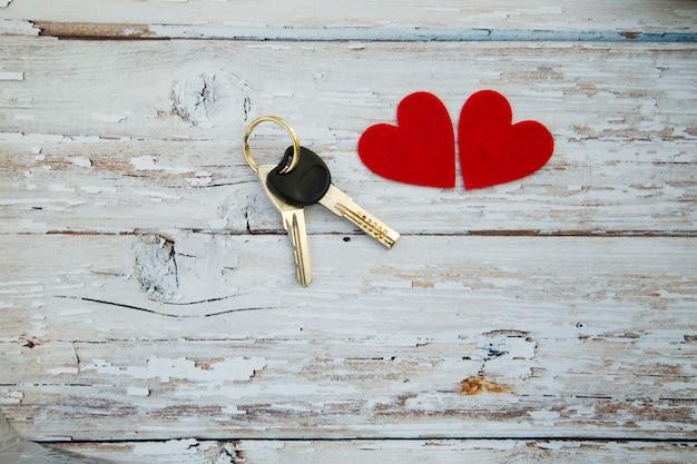 Molho de chaves de casa com corações em fundo de madeira