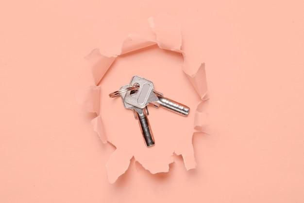 Molho de chaves de metal por um buraco rasgado em papel rosa baunilha