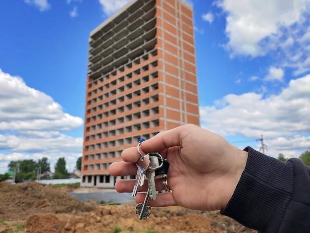 Molho de chaves de um apartamento na mão de um homem no fundo de um novo edifício