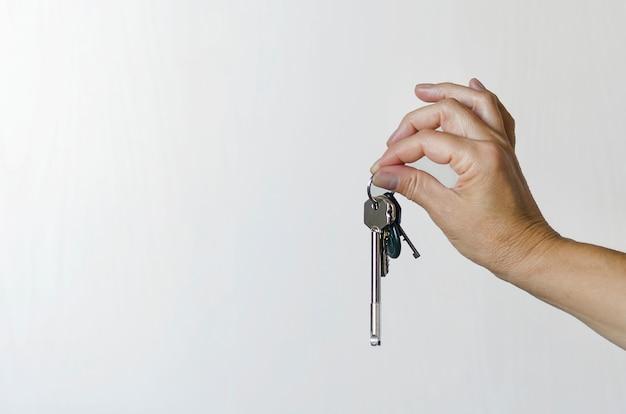 Molho de chaves em uma mão feminina sobre um fundo claro. vida nova. copie o espaço