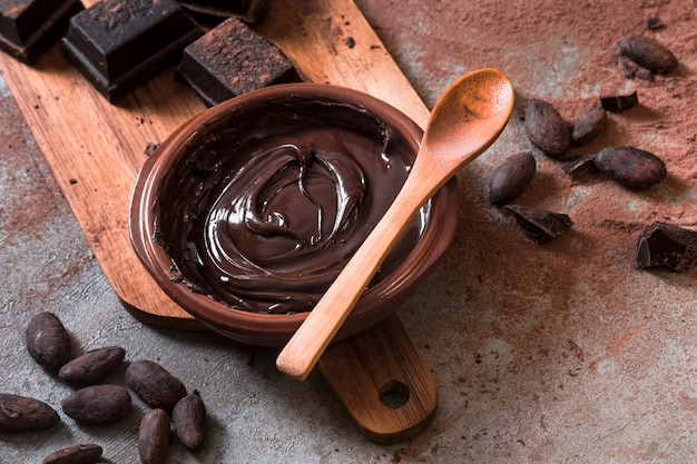 Molho de chocolate com pedaços de barra de chocolate e grãos de cacau