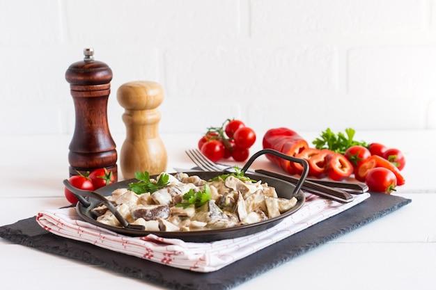 Molho de cogumelos com creme e queijo em uma frigideira sobre uma mesa branca.