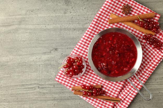 Molho de cranberry e ingredientes na mesa texturizada cinza