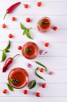 Molho de ketchup de tomate com tomate cereja e red hot chilli peppers, alho e ervas em uma jarra de vidro na mesa branca. molho de tomate caseiro e tomates frescos. . vista plana, vista superior