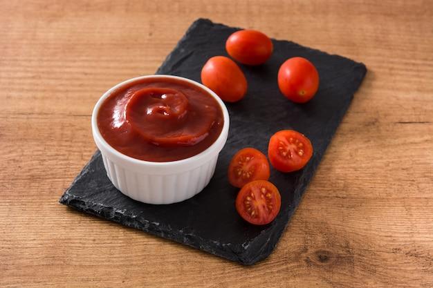 Molho de ketchup na tigela e tomate na mesa de madeira