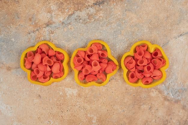 Molho de macarrão em fatias de pimentão em fundo laranja