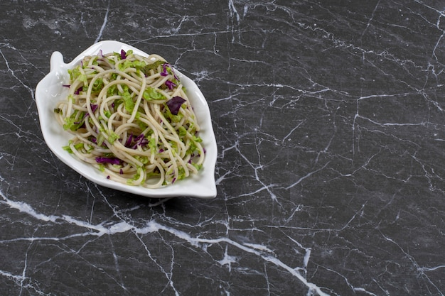 Molho de macarrão vegetal no prato sobre preto.