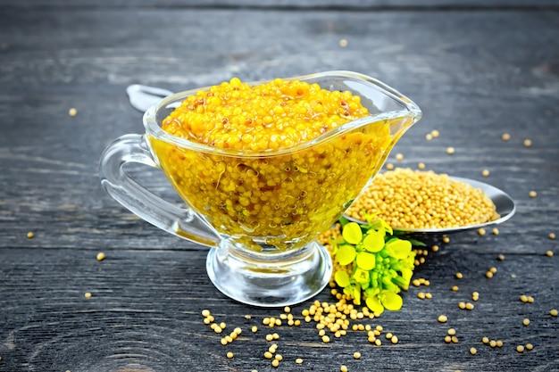 Molho de mostarda dijon em uma molheira de vidro, flores amarelas e sementes de mostarda em uma colher