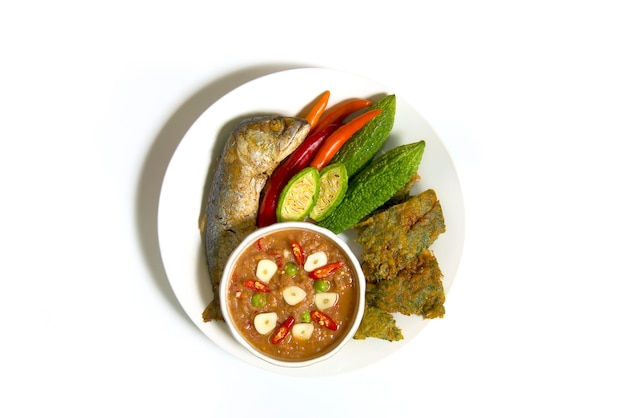 Molho de pasta de camarão e conjunto de vegetais. comida tailandesa no prato isolado no fundo branco