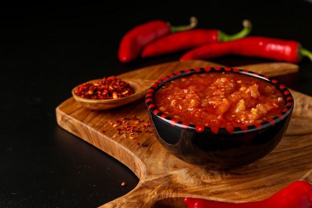 Molho de pimenta malagueta tradicional magrebino e pasta harissa na superfície escura, tunísia e culinária árabe