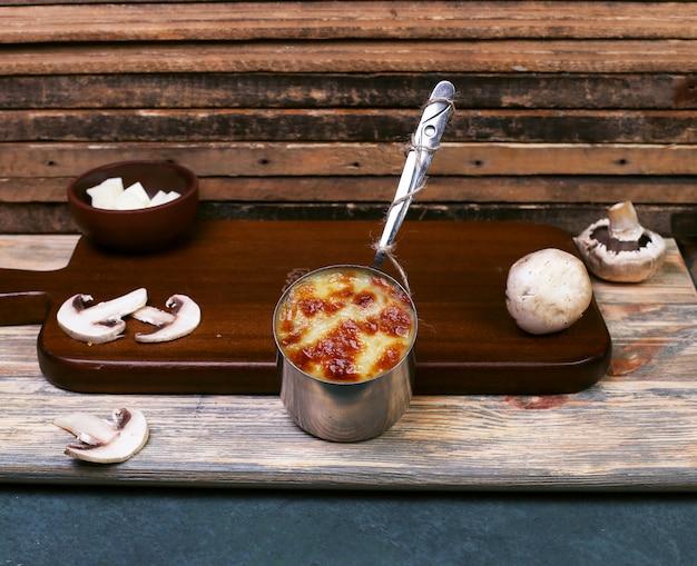 Molho de queijo com cogumelos em uma panela metálica.