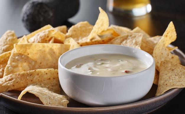 Molho de queijo queso blanco quente mexicano com tortilhas de milho no prato