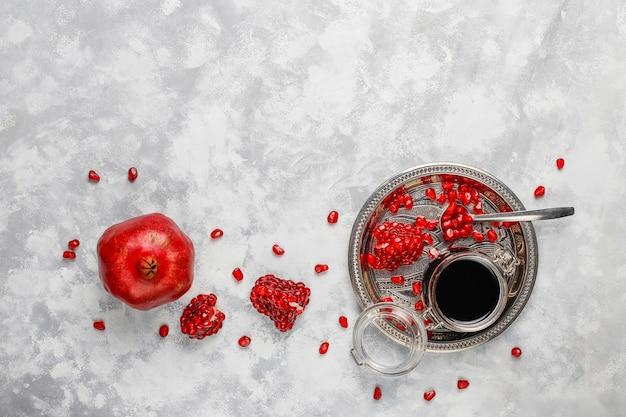 Molho de romã doce ou xarope para carne e peixe chamado narsharab, em uma jarra de vidro com romã purificada, foco seletivo