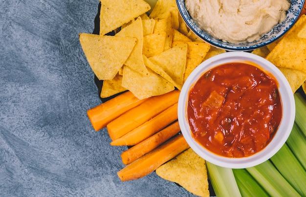 Molho de salsa em tigela sobre cenoura; talo de aipo e tortilla chips em placa