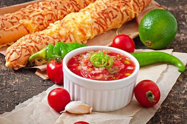 Molho de salsa na tigela de pão e queijo gruda no fundo de madeira