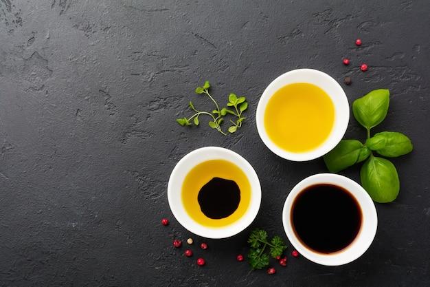 Molho de soja, azeite e molho balsâmico com ervas manjericão, salsa, pimenta e tomilho em tigelas de cerâmica branca sobre pedra preta ou superfície de concreto.