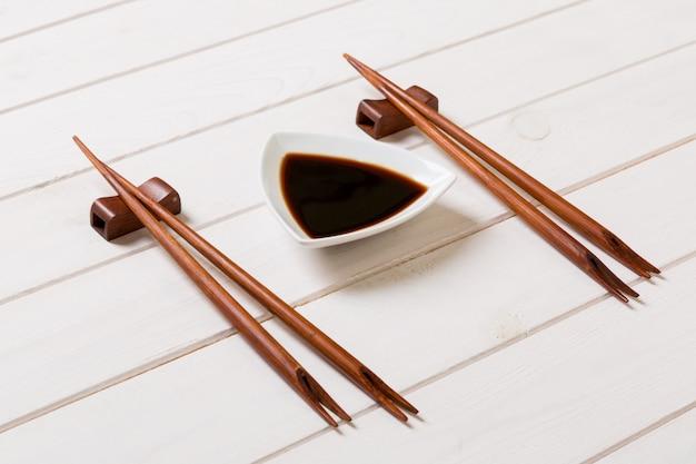 Molho de soja com pauzinhos no fundo da mesa de madeira branca