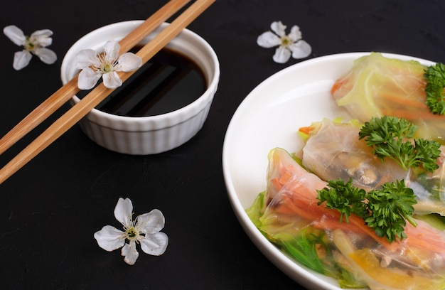 Molho de soja com rolinhos primavera em um prato branco com flores de cerejeira