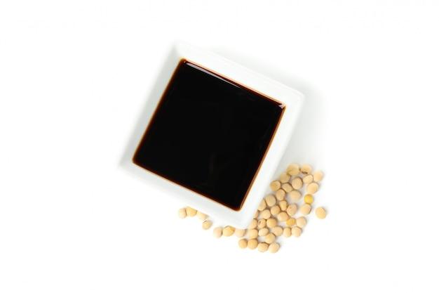 Molho de soja e grãos de soja, isolados no fundo branco