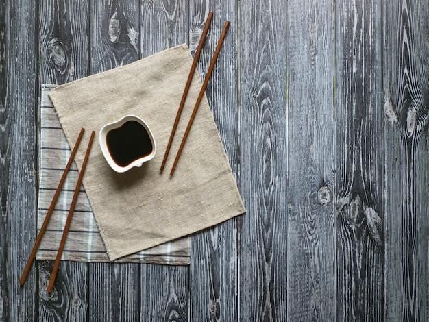 Molho de soja e pauzinhos em uma mesa de madeira escura com espaço de cópia.