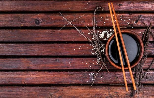 Molho de soja e pauzinhos na mesa de madeira