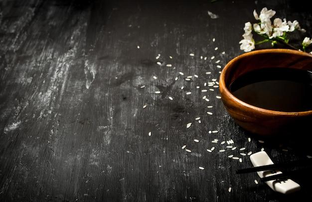 Molho de soja e ramos de flores de cerejeira. sobre um fundo preto de madeira.