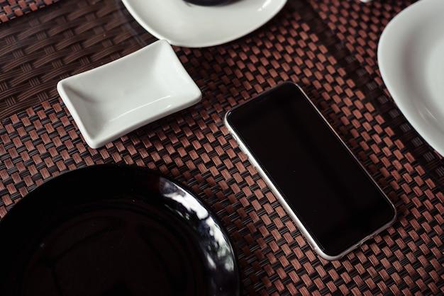 Molho de soja em um copo branco sobre um antigo fundo escuro de madeira com sushi de pauzinhos e rolos.