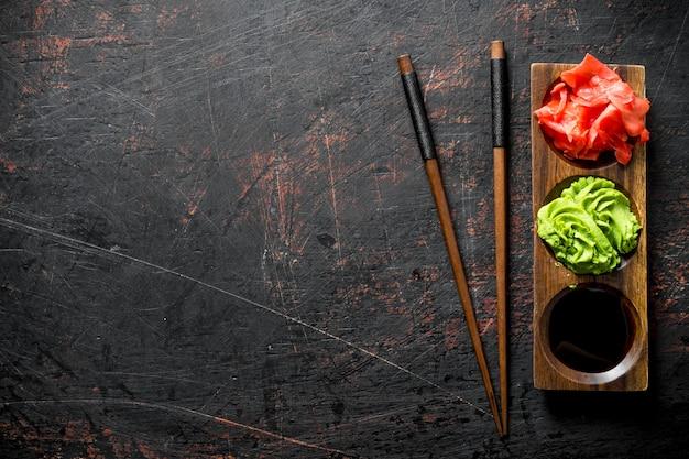Molho de soja, gengibre e wasabi em uma estante de madeira com pauzinhos. em rústico escuro