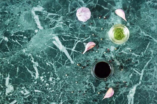 Molho de soja, óleo, alho e pimenta no fundo de pedra de mármore. vista do topo