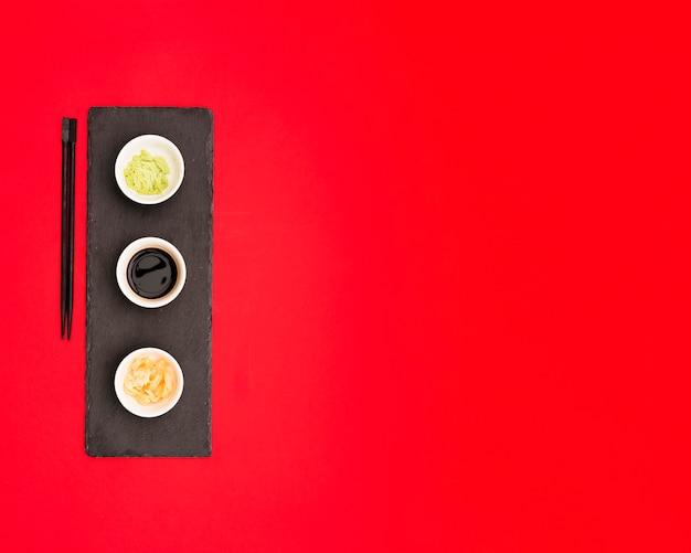 Molho de soja; wasabi e gengibre em uma placa de pedra sobre o pano de fundo vermelho com espaço para texto