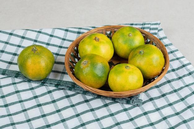 Molho de suculentas tangerinas em uma cesta de madeira