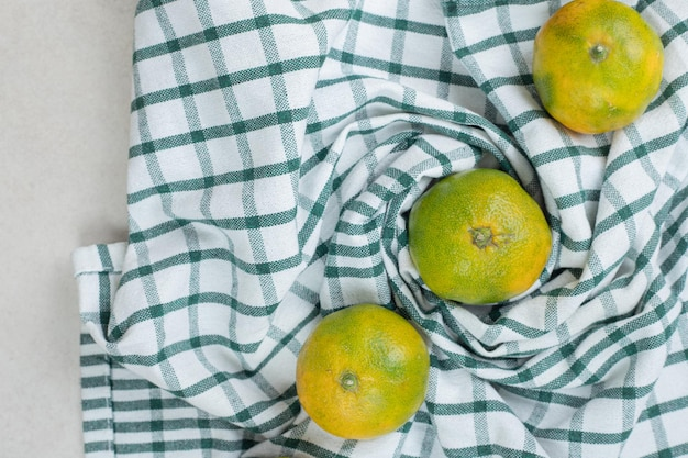 Molho de suculentas tangerinas em uma toalha de mesa listrada