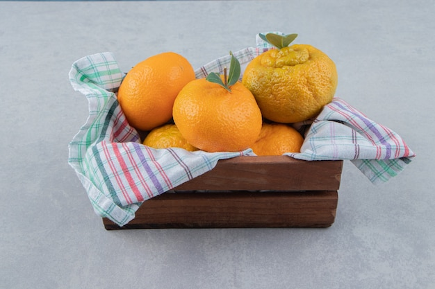 Molho de tangerinas frescas em caixa de madeira