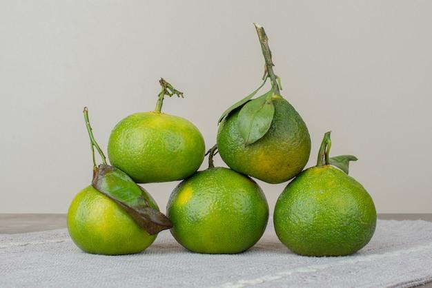 Molho de tangerinas frescas na toalha de mesa cinza