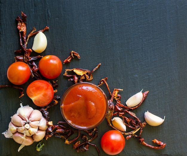 Molho de tomate com alho e pimenta seca na ardósia escura, vista superior