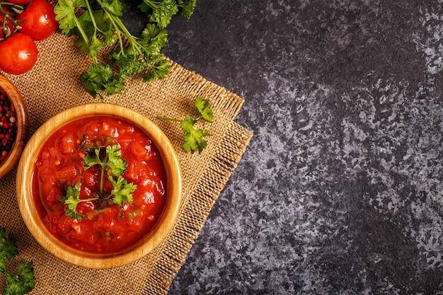 Molho de tomate com alho e salsa em uma tigela de madeira