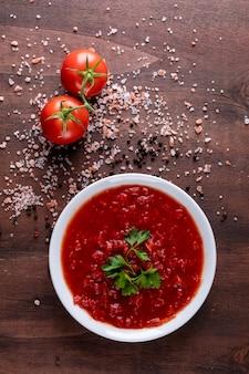 Molho de tomate e tomate cereja espalhado pimenta em pó na superfície da pedra marrom