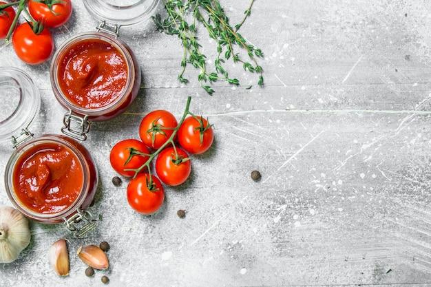 Molho de tomate em uma jarra de ervas, alho e cereja. em rústico
